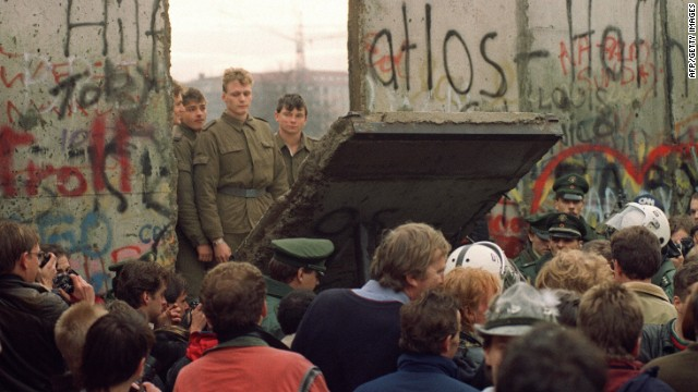 West Berliners crowd in front of the Berlin Wall early 11 November 1989 as they watch East German border guards demolishing a section of the wall in order to open a new crossing point between East and West Berlin.