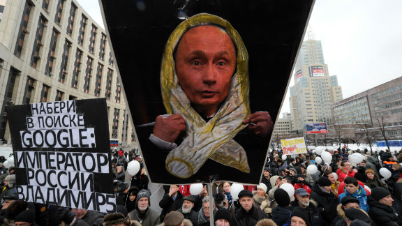 Protesters hold banners mocking Russian Prime Minister Vladimir Putin.