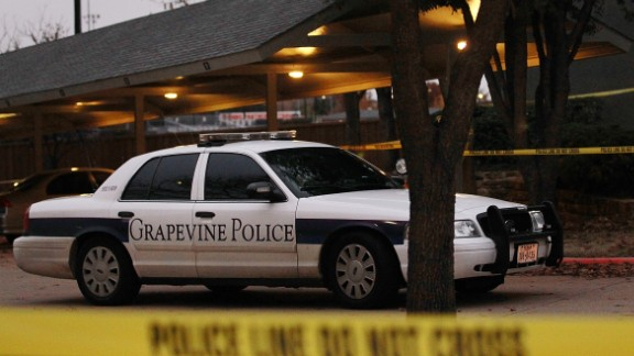Police officers investigate an apartment building where seven people were found dead on Christmas Day in Grapevine, Texas.