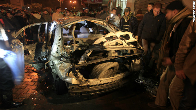 Palestinians look at a damaged car in Beit Lahia in the northern Gaza Strip after an Israeli airstrike on Tuesday.