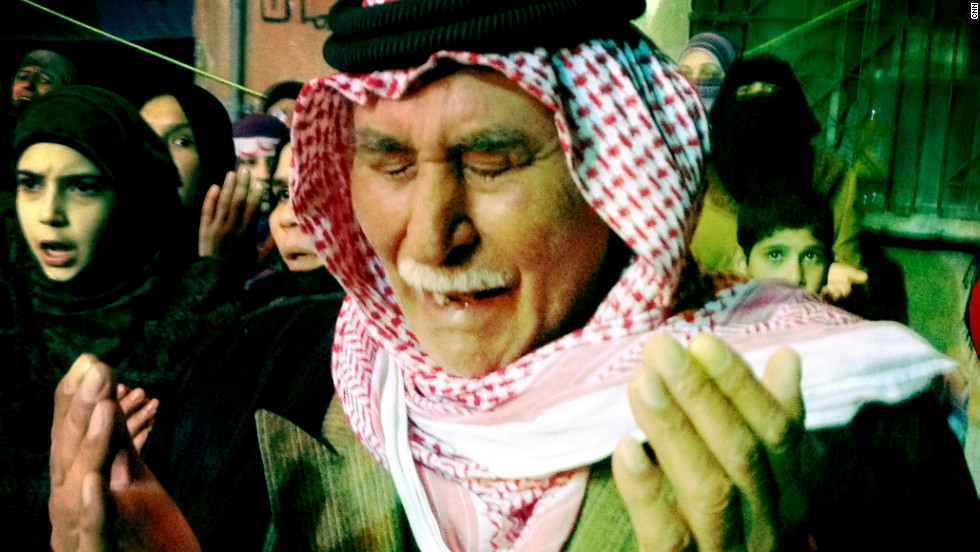 An old man prays at a night demonstration in the Al Khaledia neighborhood in Homs, Syria