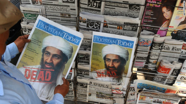 A Pakistani man reads a newspaper displaying news of the death of Osama bin Laden at a stall in Lahore on May 3, 2011.
