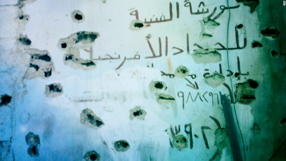 A bullet-marked wall is pictured in Baba Amr.