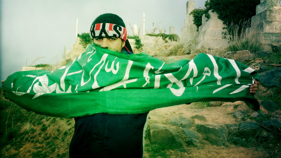 "A mourner holds aloft a green flag with Islamic verses at the funeral of ""Malik"" in Dar al-Kabira."