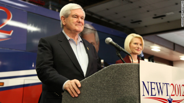 Newt Gingrich, campaigning in Iowa with his wife Callista, has been the target of negative advertising.