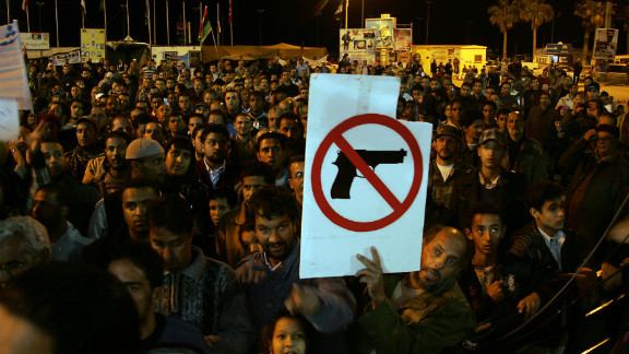 A Libyan demonstrator holds a sign at a protest in Benghazi calling for the disarmament of militiamen, December 13, 2011