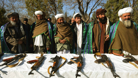 Taliban fighters stand near their weapons after joining Afghanistan government forces at a ceremony in Herat on December 29.