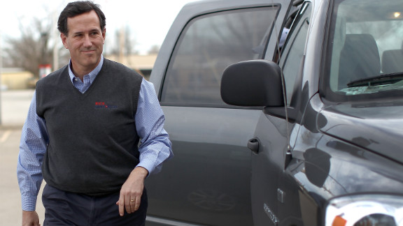 Santorum strides confidently out of a pickup truck in Knoxville, Iowa, in a gray sweater vest embroidered with his name. Guess his mom doesn't have to write on the tag anymore ...
