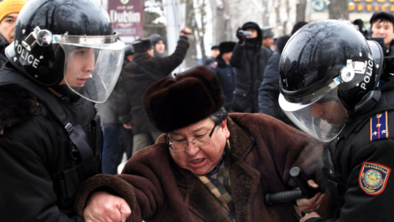 Kazakh riot policemen detain an opposition supporter during a rally in Almaty on December 17, 2011.