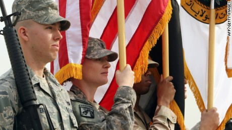 U.S. soldiers hold the U.S. and Iraqi flags during a symbolic flag-lowering ceremony marking the end of the U.S. mission in Iraq at a military base West of Baghdad on December 15, 2011.