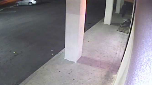 Police say this surveillance camera photo shows the suspect standing near one of his victims December 20.