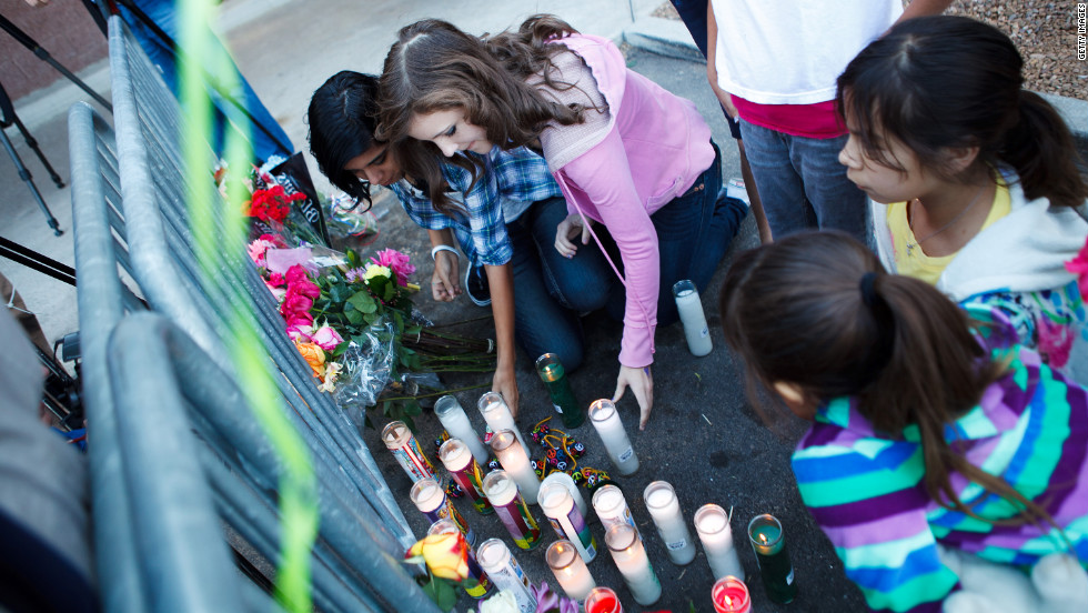 A group of local children light candles at the Safeway memorial site.