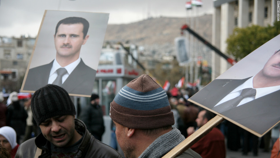 Supporters hold up photos of President al-Assad during the rally.