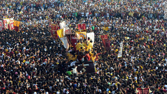 Pilgrims try to reach for a life-size icon of Jesus Christ carrying a cross during the Black Nazarene procession in Manila.