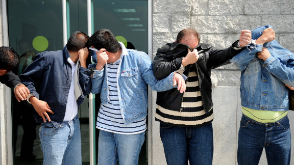 Four drug traffickers and members of the now-defunct Cali Cartel cover faces on January 15, 2009, in Bogota.