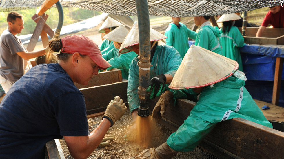 U.S. Army Staff Sgt. Nicole McMinniman, left, screens dirt with the help of local workers during recovery operations in the Savannakhet province, Laos.