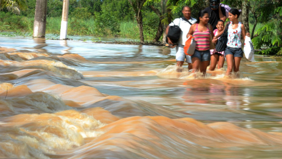 Local residents wade through a flooded street in Campos, 300 km north of Rio de Janeiro, Brazil, on January 6, 2012.