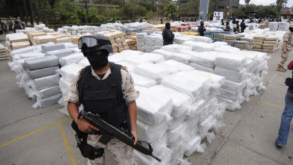 Mexican Federal Police stand guard over 105 tons of marijuana seized in Tijuana, Mexico, in October 2010. Smuggling remains a booming business. For example, south of the border it costs $2,000 to produce a kilo of cocaine from leaf to lab, according to the DEA. In America, a kilo