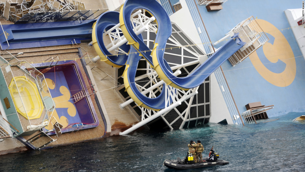 Military rescuers patrol next to the listing Costa Concordia on January 15. A spiraling water slide can be seen on the deck.