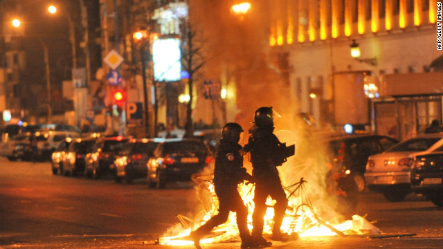 Romanian police walk past a fire lit by protesters in the center of Bucharest on January 15, 2012.