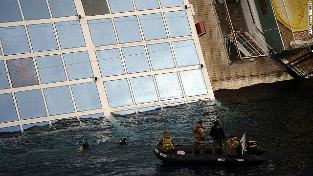 Divers inspect the Costa Concordia on Sunday. The death toll  from the disaster off the Tuscan island stands at at least six.