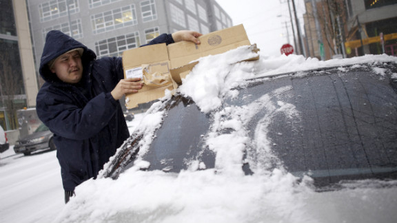 A man scrapes snow from the back window of his car in downtown Seattle on Wednesday.