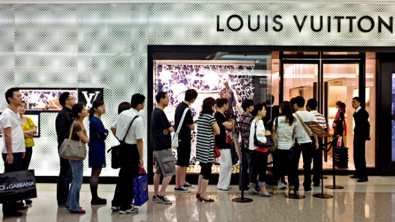 Shoppers queue to enter a shop of French luxury brand Louis Vuitton in a shopping mall in Shanghai, China.