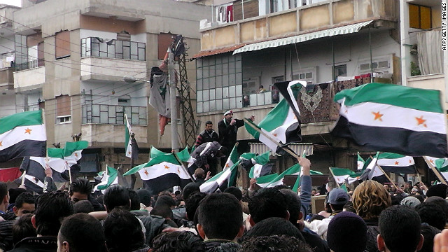 Anti-government demonstrators wave former Syrian flags in the Khalidiya neighborhood in Homs on January 20.
