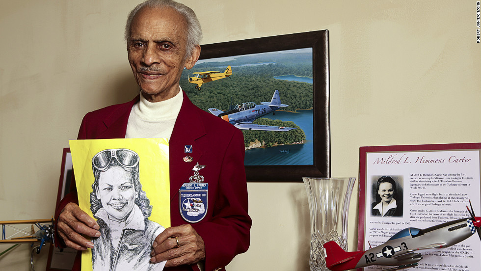 "Herbert Carter, 94, one of the original 33 Tuskegee Airmen pilots, holds a portrait of his wife, Mildred Hemmon Carter, in her flight uniform. She was the first black female pilot in Alabama and is counted among the history-making Tuskegee Airmen, too. He eventually rose to the rank of lieutenant colonel. Married nearly 70 years, the two were known as Tuskegee's ""first couple."""