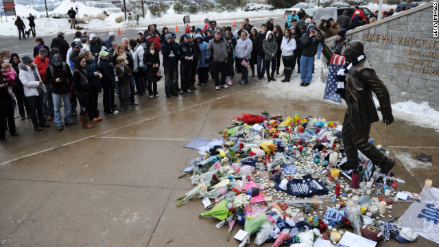 People pay their respects on Sunday at the statue of former Penn State football coach Joe Paterno after news of his death.