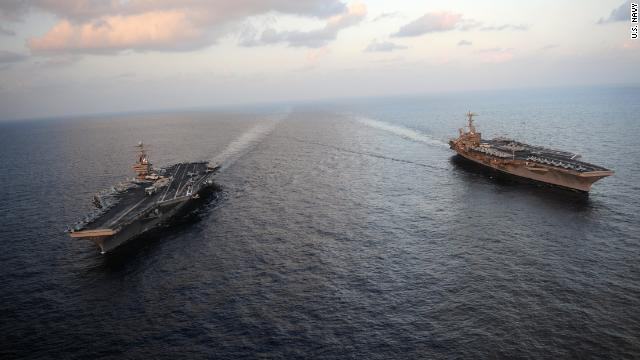 The USS Abraham Lincoln, at left with the John Stennis in the Arabian Sea, moved through the Strait of Hormuz on Sunday.