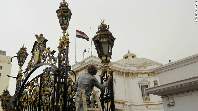 A worker cleans the gate leading to the parliament building in Cairo ahead of the first post-Mubarak session.