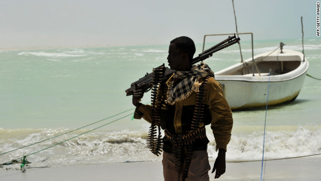 A Somali, part armed militia, part pirate, carries his high-caliber weapon on a beach in the central Somali town of Hobyo last year.