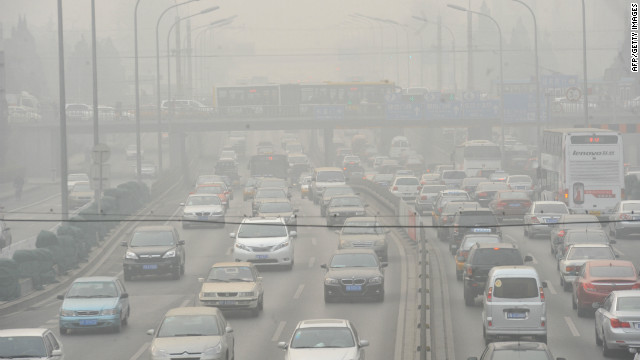 Vehicles make their way along a road on a smoggy day in Beijing on January 18.