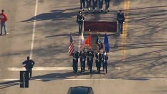 Honor guard memebers carry flags ahead of Saturday's homecoming parade in St. Louis.