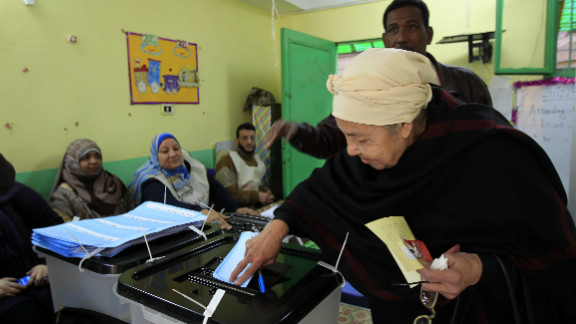 An Egyptian woman casts her ballot at a polling station in Cairo