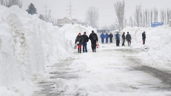 Freshly plowed snow frames a road in Bucharest on January 27.