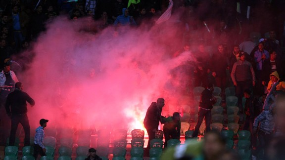 Flares are thrown in the stadium during clashes that erupted after a football match between Egypt