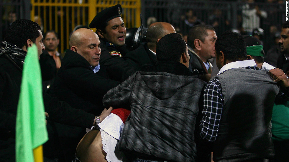 An Egyptian policeman intervenes as people try to separate rival football fans.