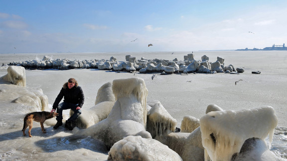 A man pets a dog next to frozen sea waters in Constanta, Romania, on Wednesday. Temperatures plunged to -34 degrees Celsius (-29 degrees Fahrenheit) in central Romania.