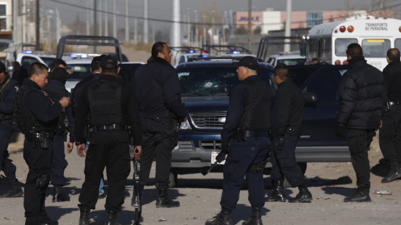 Municipal police officers in Ciudad Juarez, Mexico, collect evidence from a shooting that left colleague Julian Juarez Baena dead.