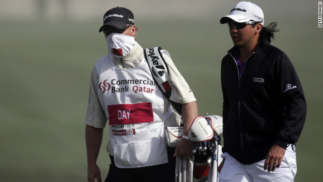 Australian Jason Day and his caddie leave the course after play was called off due to high winds.
