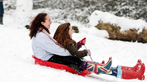 Two girls sled down the hill Sunday in London