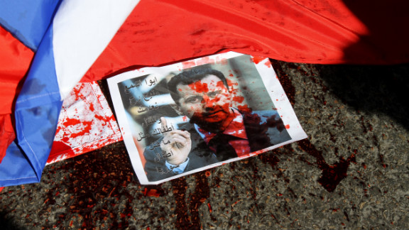 A picture of Syria's embattled President Bashar al-Assad sprayed with red paint lies next to a Russian flag about to be set on fire by protesters outside the Russian embassy in Beirut on February 5.
