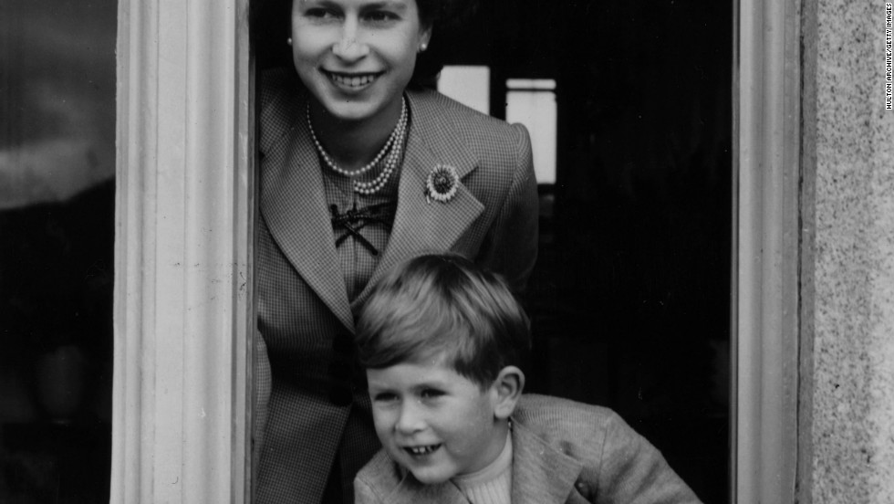 28th September 1952: Queen Elizabeth II and her son Charles leaning out of a window at Balmoral Castle, Scotland.