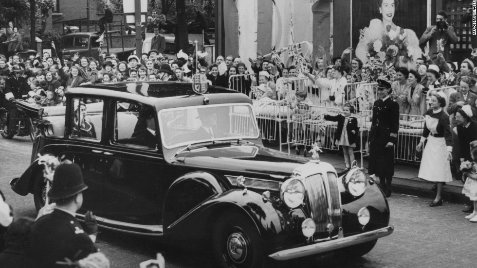 4th June 1953: Children wave as Queen Elizabeth II passes by in her car, at North Kensington, London.