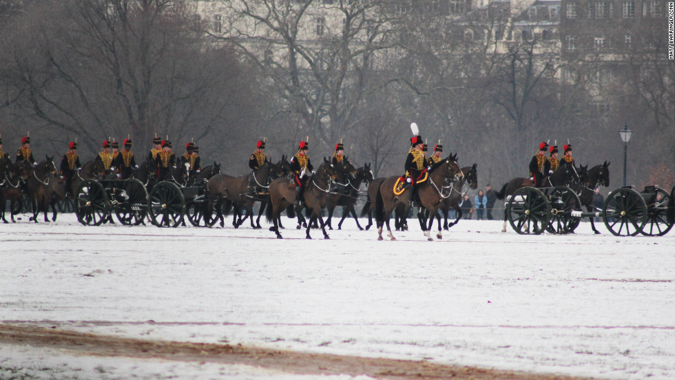 With snow lying heavy underfoot, the King's Troop Royal Horse Artillery trot into position in Hyde Park as part of the annual Accession Day celebrations.