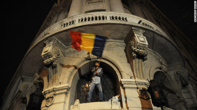 A protester waves the Romanian flag from a window of Bucharest University headquarters in Bucharest earlier this year