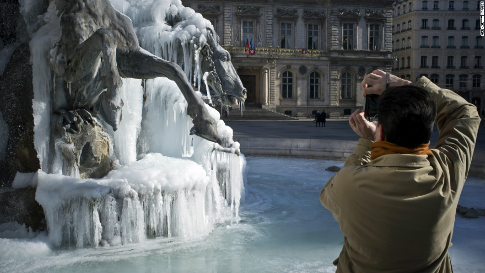 A man takes pictures of a Bartholdi fountain covered by ice on February 6, 2012 on Terraux square in Lyon, eastern France. In France, 39 of the country's 101 regions were on alert for deep cold or snow, down from more than half the regions at the weekend.