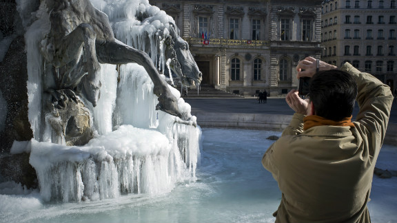 A man takes pictures of a Bartholdi fountain covered by ice on February 6, 2012 on Terraux square in Lyon, eastern France. In France, 39 of the country